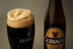 Ein volles Glas Guinness und eine leere Flasche