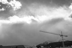 Der Berg im grauen Dunst, davor der Arm eines Krans, darüber sonnig